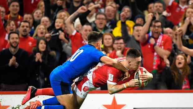 Wales' Josh Adams scores his side's first try as he is challenged by Italy's Tommaso Allan. Photo: Getty Images