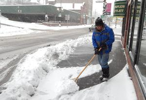 In a photo from Nov. 11, 2014, Alan Messner shovels the sidewalk in front of Surplus Outlet in downtown Houghton, Mich. (AP Photo/Daily Mining Gazette, Dan Roblee)