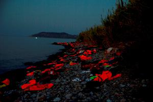 Lifevests that have been used by migrants crossing from Turkey to Greece are seen on the beach of the island of Lesbos, Saturday, Sept. 19, 2015. (AP Photo/Petros Giannakouris)