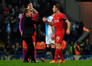 Liverpool's Northern Irish manager Brendan Rodgers (L) celebrates on the pitch with Liverpool's English midfielder Jordan Henderson (R) after the English FA Cup quarter-final replay football match between Blackburn Rovers and Liverpool at Ewood Park in Blackburn, north west England on April 8, 2015. Liverpool won the game 1-0. AFP PHOTO / PAUL ELLIS  RESTRICTED TO EDITORIAL USE. NO USE WITH UNAUTHORIZED AUDIO, VIDEO, DATA, FIXTURE LISTS, CLUB/LEAGUE LOGOS OR LIVE SERVICES. ONLINE IN-MATCH USE LIMITED TO 45 IMAGES, NO VIDEO EMULATION. NO USE IN BETTING, GAMES OR SINGLE CLUB/LEAGUE/PLAYER PUBLICATIONS.PAUL ELLIS/AFP/Getty Images