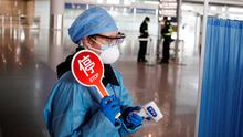A staff member wears protective gear at the temperature check station of the arrival hall in Beijing Capital Airport as the country is hit by an outbreak of the novel coronavirus. REUTERS/Thomas Peter