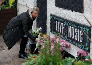 A woman lays flowers at the Clutha pub in Glasgow, Scotland, as a service is held in at Glasgow Cathedral marking the first anniversary of the helicopter crash that caused that caused the death of ten people. Photo: Danny Lawson/PA