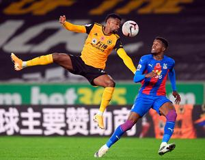 Wolves' Nelson Semedo rises to meet the ball ahead of Crystal Palace's Wilfried Zaha. Photo: PA
