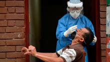 RESPONSE: A health worker takes a sample for a Covid-19 test. Only adequate testing and tracing or lockdown can slow this virus. Photo: RAUL ARBOLEDA/AFP via Getty Images