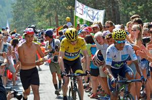 A fan encourages Team Sky rider Chris Froome, the overall leader's yellow jersey holder, and Movistar rider Nairo Quintana.