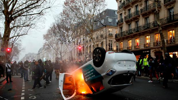 """An overturned car burns during a demonstration by the """"yellow vests"""" movement at Boulevard Saint Germain in Paris, France, January 5, 2019. REUTERS/Gonzalo Fuentes"""