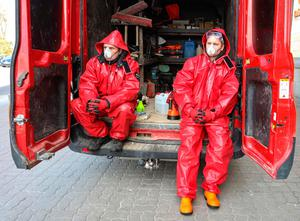 Workers, wearing a protective suit, wait before disinfecting a bus in Vilnius, Lithuania  (Photo by PETRAS MALUKAS/AFP via Getty Images)