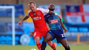 Fleetwood Town's Glenn Whelan (left) and Wycombe Wanderers Fred Onyedinma battle for the ball during the Sky Bet League One play-off semi-final, second leg match at Adams Park, Wycombe.