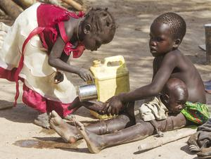 Displaced siblings wash their brother in an IDP camp in Twic County of South Sudan. Photo: Mark Condren