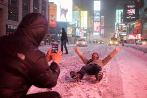 Valentin Borriello, from Paris, France, has his photograph made by a friend while lying on 7th Ave during snow storm in Times Square, New York early morning January 26, 2015.   REUTERS/Adrees Latif