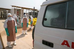 Healthcare workers prepare to disinfect an ambulance transporting a newly admitted Ebola patient at the entrance to the Save the Children Kerry Town Ebola treatment centre outside Freetown, Sierra Leone (REUTERS/Baz Ratner)