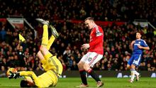 Chelsea goalkeeper Thibaut Courtois holds onto the ball after making a save as Manchester United's Wayne Rooney looks on