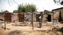 A woman stands in front of a burnt building in Michika town, after the Nigerian military recaptured it from Boko Haram, in Adamawa state May 10, 2015. Reuters/Akintunde Akinleye