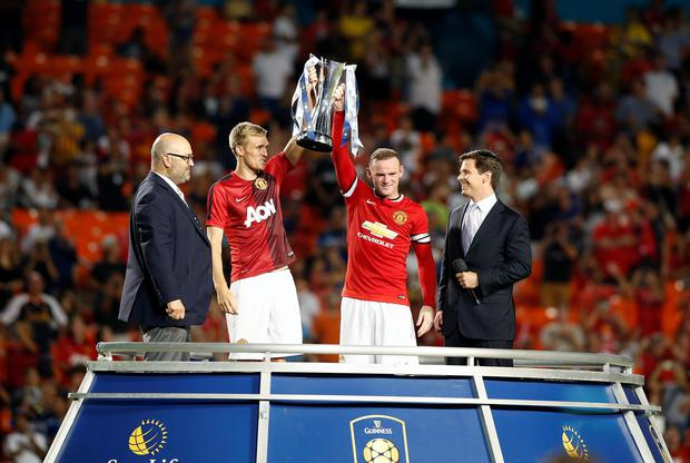 Manchester United's Wayne Rooney (right) holds the championship trophy with midfielder Darren Fletcher