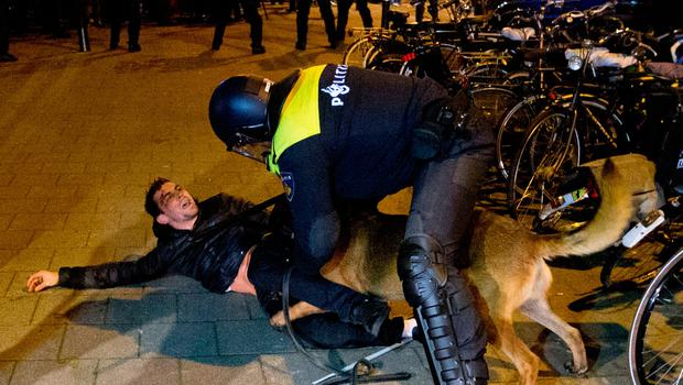 A Dutch riot policeman tries to get his dog to let go of a man after riots broke out during a pro Erdogan demonstration at the Turkish consulate in Rotterdam, Netherlands (AP Photo/Peter Dejong)