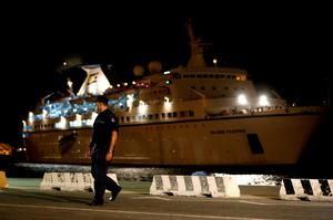 A policeman walks as a ship, that picked up some 345 migrants from a small boat stranded off the southwestern coast of Cyprus, arrives at the Mediterranean island's port of Limassol on Thursday, Sept. 25, 2014. (AP Photo/Petros Karadjias)