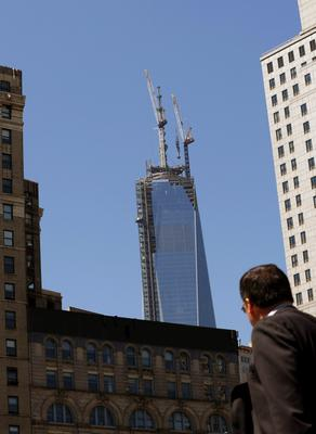A man watches as the final section of the spire that will top off One World Trade Center is raised to the top of the building in New York