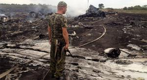 An armed pro-Russian separatist stands the Malaysia MH17 crash site