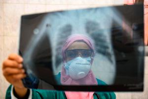 An Egyptian doctor wearing two protective masks checks a patient's lung X-ray at the infectious diseases unit of the Imbaba hospital in the capital Cairo, during the COVID-19 coronavirus pandemic crisis. (Photo by AHMED HASAN/AFP via Getty Images)