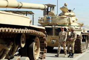 Egyptian army soldiers walk next to some tanks