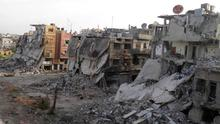 A view of a street piled with damaged buildings in Homs