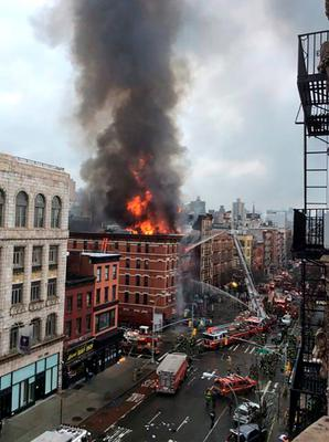 Fire shoots from the roof of a building after it collapsed and burst into flames in New York City's East Village as seen in this picture taken by Scott Westerfeld. Reuters/Scott Westerfeld