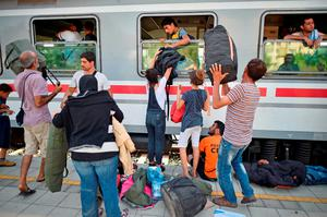 BELI MANASTIR, CROATIA - SEPTEMBER 18:  Migrants pass luggage through windows as they board trains at the train station in Beli Manastir, near Hungarian border on September 18, 2015 in Beli Manastir,Croatia. Officials are saying that they had no choice than to close eight road border crossings yesterday after more than 11,000 people entered the country since Hungary fenced off its border with Serbia earlier this week.  (Photo by Jeff J Mitchell/Getty Images)