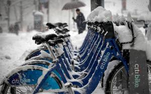 Citibikes are parked in a base station during a morning snow storm in New York's financial district