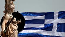 A Greek national flag flutters next to a statue of ancient Greek goddess Athena, in Athens May 21, 2015.