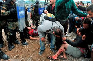 Migrants clash with Macedonian police at the Greek-Macedonian border near the town of Idomeni, northern Greece, on August 21, 2015. Macedonian police have reinforced control at the border with Greece in a bid to stop the influx of migrants, but a few hundred Syrians managed to cross the frontier overnight into August 21. Police prevented reporters to access a no-man's land where on August 20, officers had been in a standoff with about 1,500 migrants and refugees who wanted to cross into Macedonia. AFP PHOTO /SAKIS MITROLIDISSAKIS MITROLIDIS/AFP/Getty Images