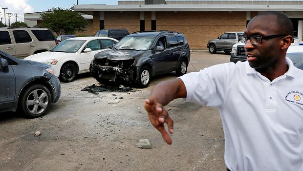 Shawn Williams, with Dallas Police Community Affairs, describes the area where an explosion occured at Dallas Police headquarters during an early morning attack by a gunman Saturday, June 13, 2015, in Dallas. (AP Photo/Ron Jenkins)
