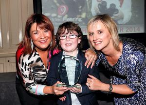RTE's Brenda Donohue and Dolores Madden, marketing manager, Hidden Hearing presenting the 2014 Hidden Hearing Heroes Award to Quaid Cleland (age 9)
