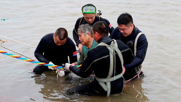 A woman is helped after being pulled out by divers from a sunken ship in Jianli, Hubei province, China. Photo: Reuters