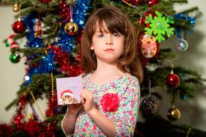 Shocked: Florence Widdicombe (6) with a card from the same pack as one that contained a message from a Chinese prisoner. Photo: Dominic Lipinski/PA Wire
