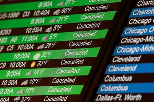Flight cancellations are seen on an electronic flight board at LaGuardia Airport in New York, February 13, 2014. A deadly winter storm moved north along the East Coast of the United States on Thursday, bringing heavy snow, sleet and rain across the Washington, D.C., and New York areas, grounding flights and shutting government offices. REUTERS/Shannon Stapleton    (UNITED STATES - Tags: ENVIRONMENT SOCIETY)