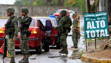 "Soldiers stand guard as others inspect a vehicle at a checkpoint in Acapulco, Mexico, July 12, as Mexico's most notorious drug lord, Joaquin ""El Chapo"" Guzman, broke out of a high security prison on Saturday night for the second time (REUTERS/Claudio Vargas)"