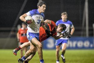 Waterford's Shane Aherne ploughs forward past the tackle of David Harrington, UCC