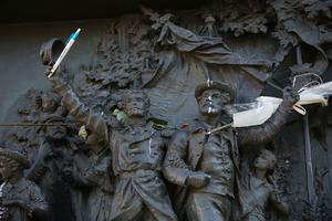 A statue is modified with a pen in a show of defiance as demonstrators gather in Place de la Republique prior to a mass unity rally to be held in Paris following the recent terrorist attacks
