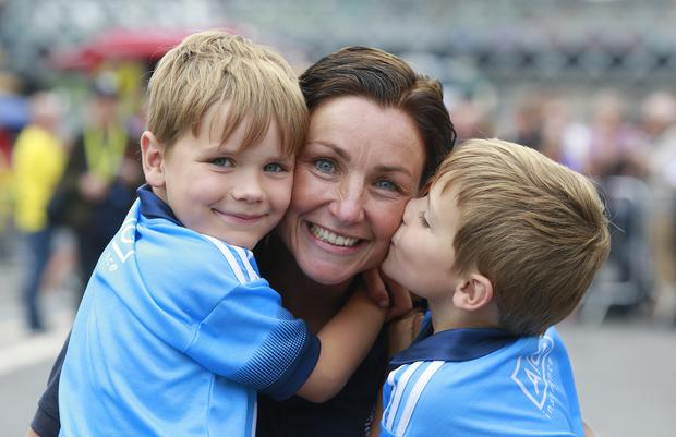 Rachel Lee, from Malahide, is congratulated by her sons, Bruce, left and Rex after competing in the Liffey swim in Dublin. Picture credit; Damien Eagers / INM