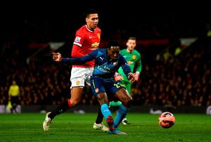 Danny Welbeck holds off the challenge of Manchester United defender Chris Smalling to score Arsenal's winning goal in the FA Cup quarter-final at Old Trafford. Photo: Laurence Griffiths/Getty Images