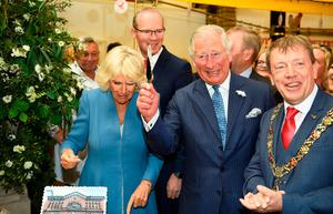Britain's Prince Charles reacts after cutting a cake during a visit to the English Market with Camilla, the Duchess of Cornwall, in Cork, Ireland, June 14, 2018. REUTERS/Clodagh Kilcoyne