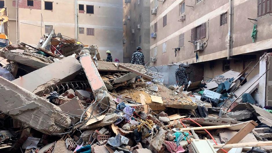 Emergency workers sift through the rubble of a collapsed apartment building in the el-Salam neighborhood in Cairo, Egypt. AP Photo