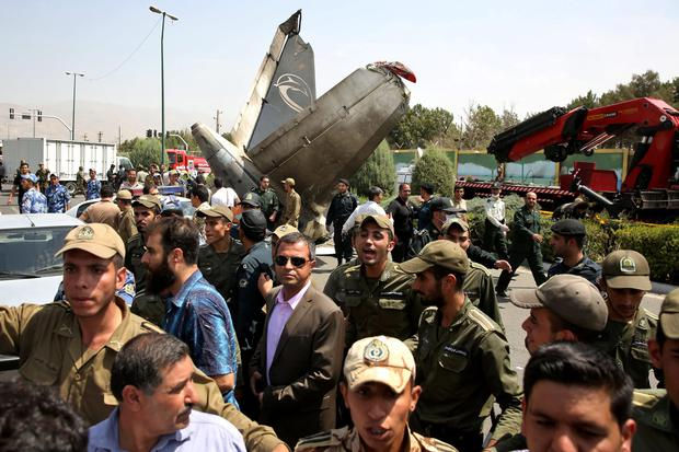 Iranian police and army soldiers direct people and media at the scene of a passenger plane crash near the capital Tehran, Iran, Sunday, Aug. 10, 2014. The Sepahan Air Iran-140 regional plane crashed Sunday killing tens of people onboard, shortly after takeoff from Tehran's Mehrabad airport on its way to Tabas, a town in eastern Iran, state media reported. (AP Photo/Ebrahim Noroozi)