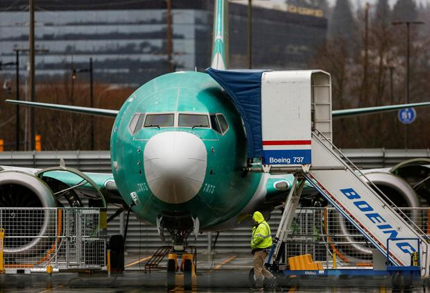 An employee walks past a Boeing 737 Max aircraft seen parked at the Renton Municipal Airport in Renton, Washington, U.S. Photo: REUTERS/Lindsey Wasson