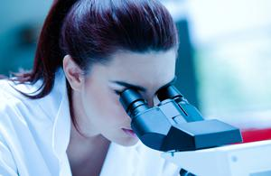 Young scientist using a microscope in a laboratory
