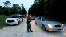 A Gilchrist County sheriff's deputy lowers the yellow tape to let vehicles through at the scene of a shooting in Bell, Florida. Don Spirit has been identified by authorities as the suspect in the incident where a 51-year-old man shot dead his daughter and six grandchildren in his home before killing himself. Photo credit: AP Photo/The Gainesville Sun, Matt Stamey