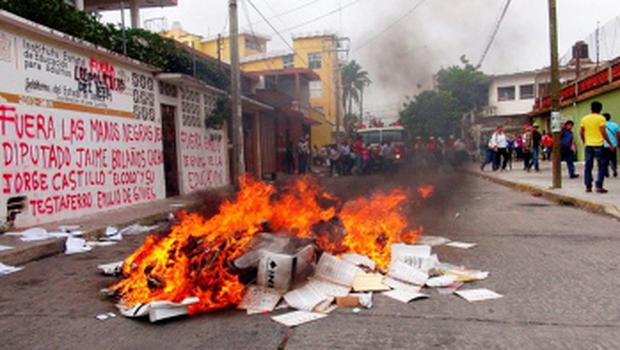 A pile of burning electoral material is seen outside the office of the National Electoral Institute (INE) in Juchitan, state of Oaxaca, June 1, 2015. Protesting teachers set fire to an office of the electoral institute and burnt electoral material in the southern Mexican state of Oaxaca as the country prepares to hold its mid-term elections on June 7 amid tension and social unrest calling for a boycott of the elections. Regional elections across several states and for the whole lower congress in Mexico are shaping up to be tense in Oaxaca, where teachers have also joined movements against education reforms proposed by President Enrique Pena Nieto. REUTERS/Stringer