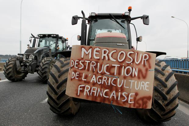 "French farmers drive their tractors on the A7 highway to protest changes in underprivileged farm area's mapping and against Mercosur talks, in PIerre-Benite near Lyon, France, February 21, 2018. Message reads, ""Mercosur - The destruction of French agriculture"".   REUTERS/Emmanuel Foudrot"
