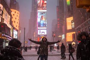 Shayan Oman, a visitor from Perth, Australia, poses for photos during a snow storm in New York's Times Square January 26, 2015. REUTERS/Adrees Latif