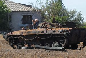 People loosen parts from a burned-out Ukrainian armored personnel carrier in the village of Hrabske, eastern Ukraine